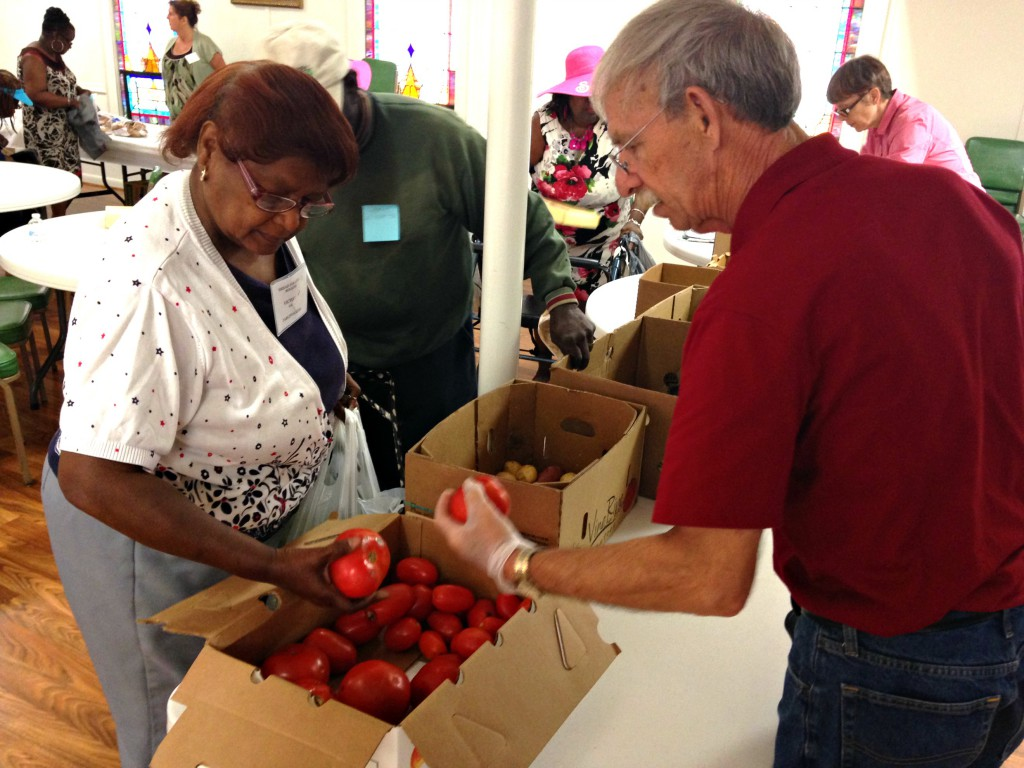 Senior picking out produce at a food pantry
