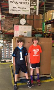 Case (right) and Harry (left) proudly weigh the food donations from their combined birthday food drive