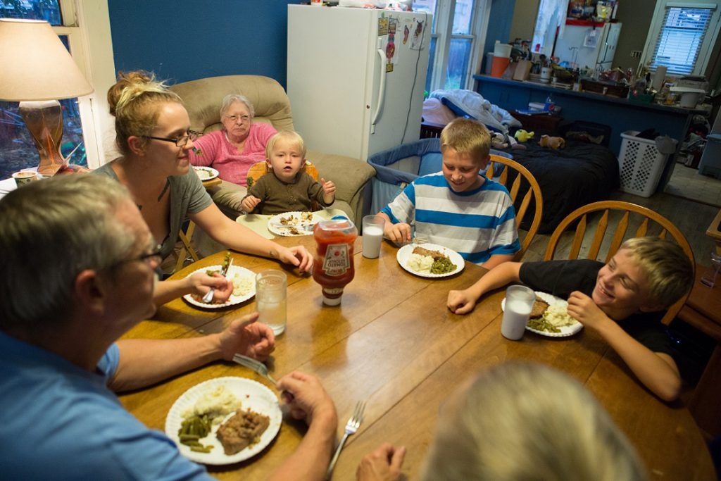 Family eating food around kitchen table