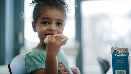 Child enjoying a summer meals sandwhich